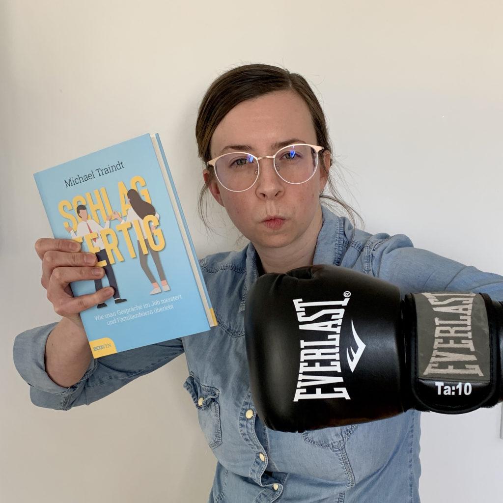 """Bild: LovelyBooks Expertin Cornelia Absmanner in Action: mit dem Sachbuch """"Schlagfertig"""" und einem Boxhandschuh"""